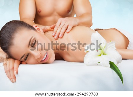 Beautiful woman with eyes closed receiving massage on a light background - stock photo