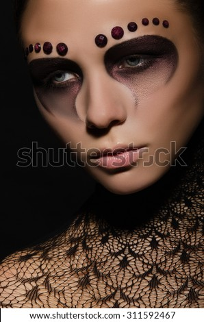 beautiful woman with face art and decorations studio shot - stock photo