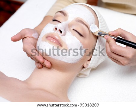 Beautiful woman with facial mask at beauty salon - stock photo
