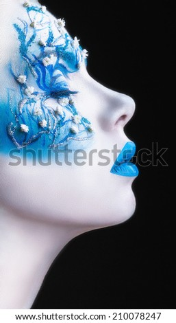 Beautiful woman with fashion make-up. White skin with blue shadows and lips on a black background - stock photo