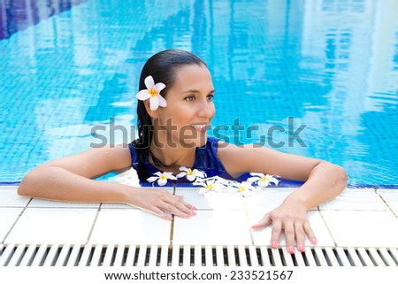 Beautiful woman with frangipani flower in hair, relaxing in the pool in full blue dress - stock photo