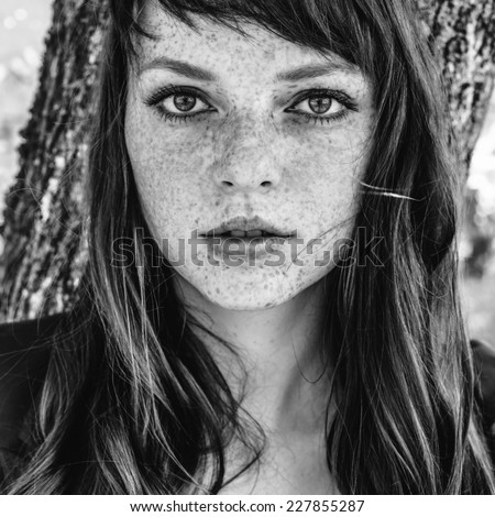 beautiful woman with freckle and in autumn park black and white - stock photo