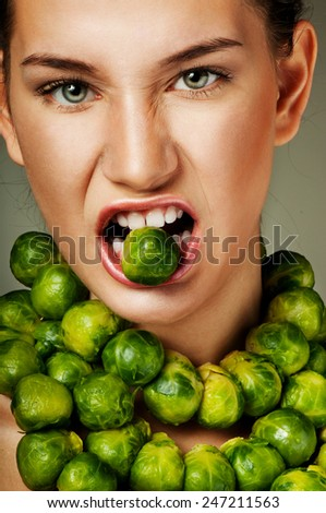 Beautiful woman with fresh Brussels sprouts. Professional makeup. Luxurious green necklace. - stock photo