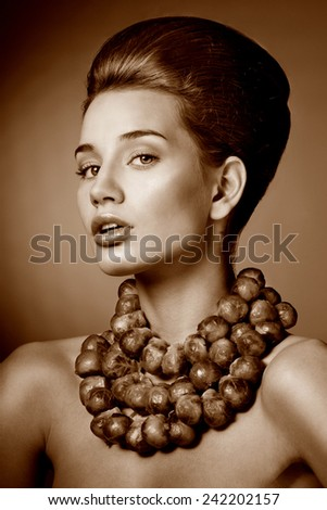 Beautiful woman with fresh Brussels sprouts. Professional makeup. Luxurious necklace. - stock photo