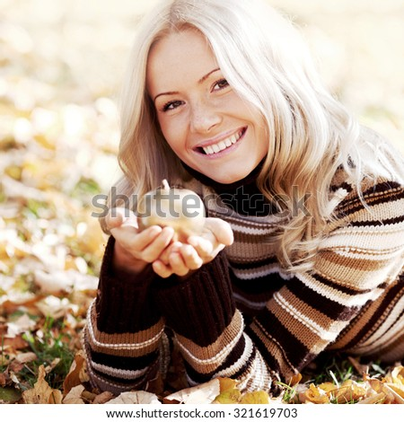 Beautiful woman with golden apple in autumn park - stock photo