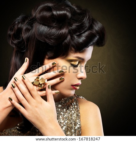 Beautiful  woman with golden nails and fashion hairstyle over creative background - stock photo