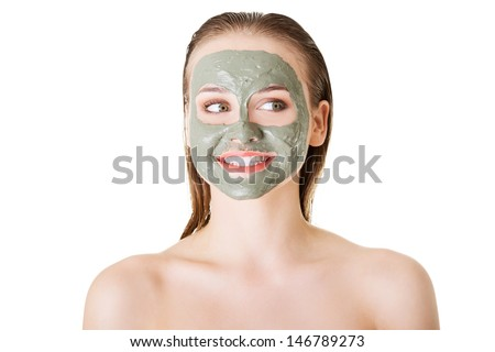 Beautiful woman with green clay facial mask, isolated on white  - stock photo