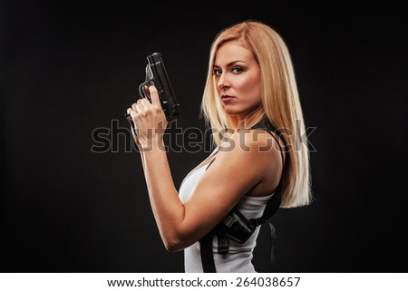 Beautiful woman with gun against black background - stock photo