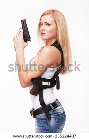 Beautiful woman with gun against white background - stock photo