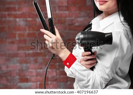 Beautiful woman with hair iron and hairdryer - stock photo