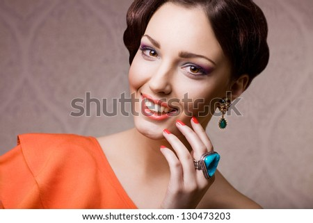 beautiful woman with hairstyle posing in studio with jewelry, close up portrait - stock photo