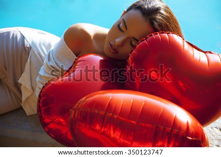 Beautiful woman with Heart balloons lying by the swimming pool.Brunette dreamy beauty. Makeup and hairstyle. Fashion and holidays style. Valentines day.Outdoors shot. Horizontal - stock photo