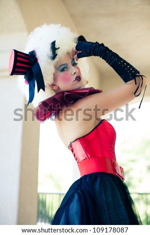 Beautiful Woman with heavy party makeup wearing a corset and Black gloves - stock photo