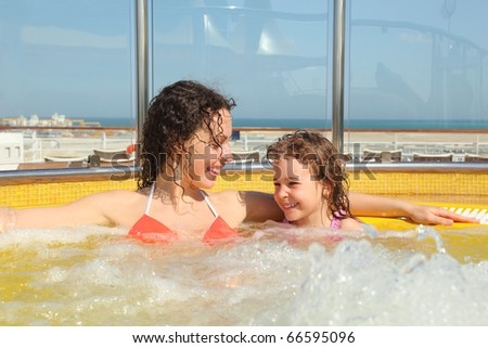 beautiful woman with her daughter both smiling in hot tub on cruise ship. - stock photo