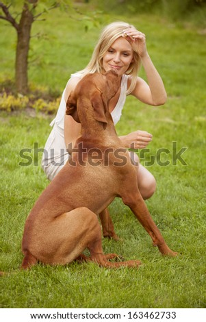 Beautiful woman with her dog on grass - stock photo