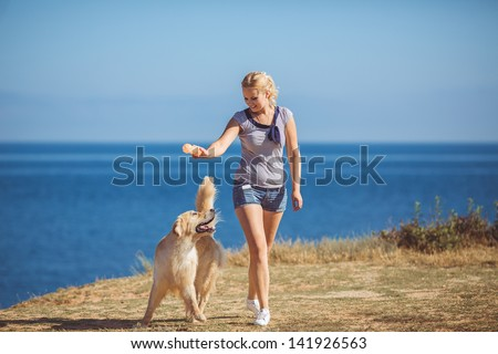Beautiful woman with her dog playing on the sea shore. Outdoor portrait - stock photo