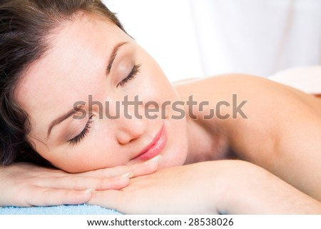 Beautiful woman with her eyes shut having rest in the spa salon - stock photo