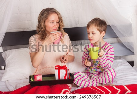 Beautiful woman with her son drinking tea in bed - stock photo