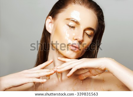 Beautiful woman with honey on her face. Healthy perfect skin. Honey treatment.  - stock photo