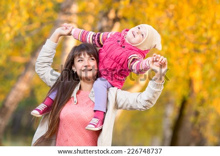 beautiful woman with kid girl outdoors in autumnal park - stock photo