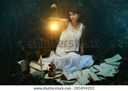 Beautiful woman with lantern in a dark forest. Surreal and fantasy - stock photo