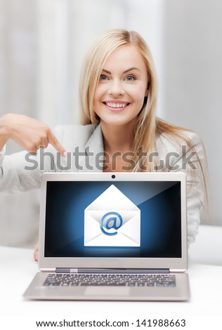 beautiful woman with laptop pointing at email sign - stock photo