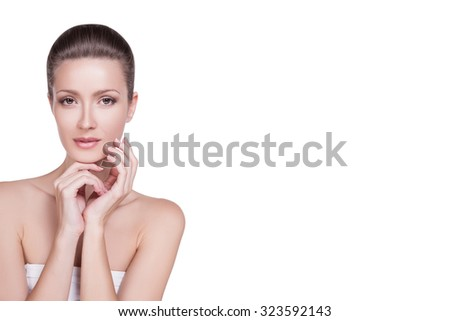 Beautiful woman with light make-up on her face on white background insulated her dark hair gathered. Portrait  woman with smooth skin and tender make-up on her face, her hand near the cheek. Beauty - stock photo