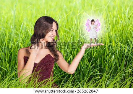Beautiful woman with little girl with fairy wings on green grass background - stock photo