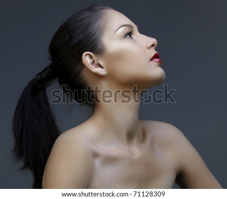 beautiful woman with long black hair in ponytail and shiny skin looking up in profile, natural make-up and beautiful skin texture - stock photo