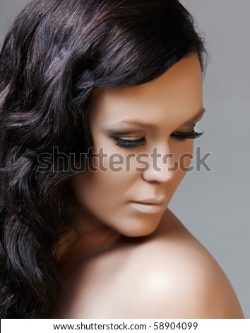 beautiful woman with long black hair looking down, from 16 Bit RAW - stock photo