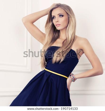 beautiful woman with long blond hair in elegant dark blue dress posing at studio - stock photo