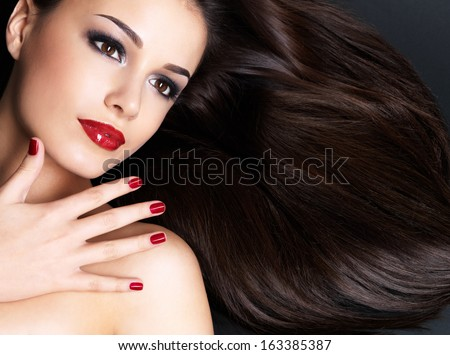 Beautiful woman with long brown straight hairs and red nails lying on the dark background - stock photo