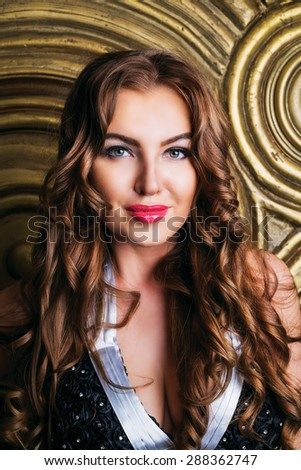 beautiful woman with long curly hair against golden wall - stock photo