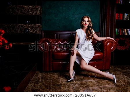 beautiful woman with long curly hair on the sofa in a luxury interior - stock photo