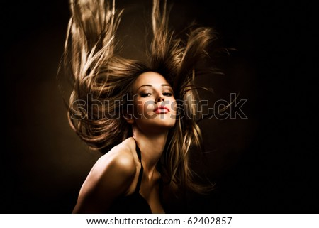 beautiful woman with long golden hair in motion, studio shot - stock photo