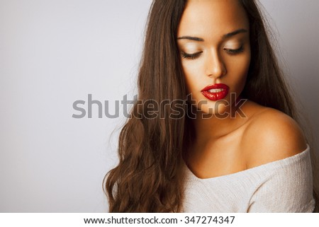 Beautiful woman with long hair and bright makeup. Red lipstick. Fashion and cosmetics style.Toned in warm colors. Copy space for your text. Horizontal. studio shot. - stock photo