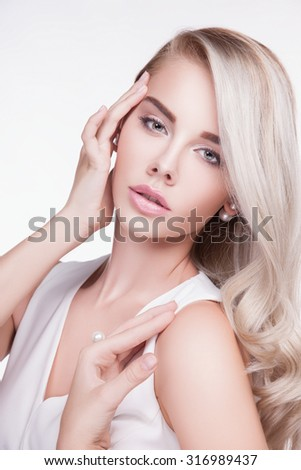 Beautiful woman with long hair.concept of beauty make-up.White hair.Attractive woman with healthy skin, studio white background, light makeup. Jewelry, beautiful young blond woman.The white dress  - stock photo