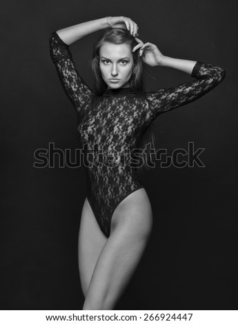 Beautiful woman with long hair in black lace lingerie, semi-dress posing in studio. Monochrome image. - stock photo