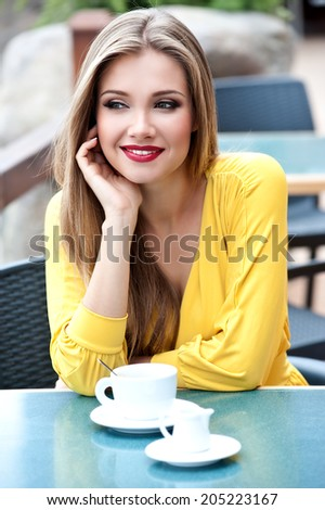 Beautiful woman with long hair in the street cafe drinking coffee - stock photo