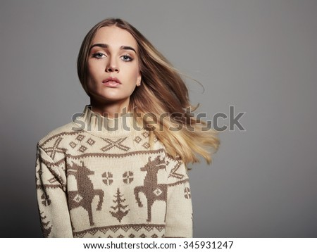 Beautiful Woman with long hair in winter pullover. Beauty Blond Girl. Healthy hair.Grey background - stock photo