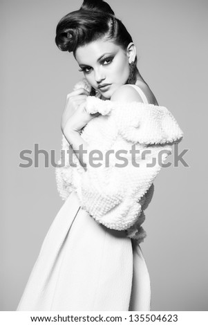 beautiful woman with long legs in white dress and fur posing in the studio - stock photo