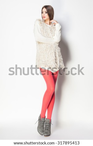 beautiful woman with long sexy legs dressed elegant posing in the studio - full body - stock photo