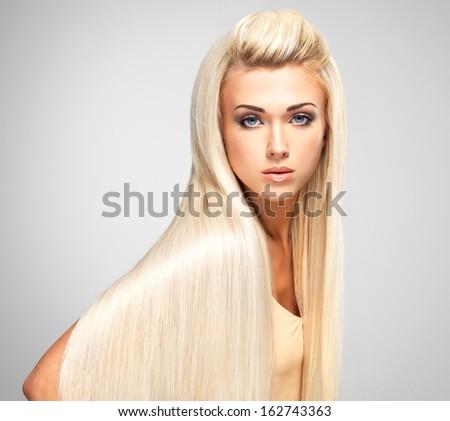 Beautiful woman with long straight blond hairs. Fashion model posing at studio. - stock photo