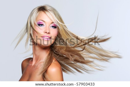 Beautiful woman with long straight hair and multi colored makeup - stock photo