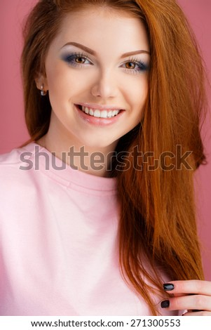 Beautiful woman with long straight red hair in a pink sweatshot. Fashion model posing at studio. Isolated on pink background - stock photo