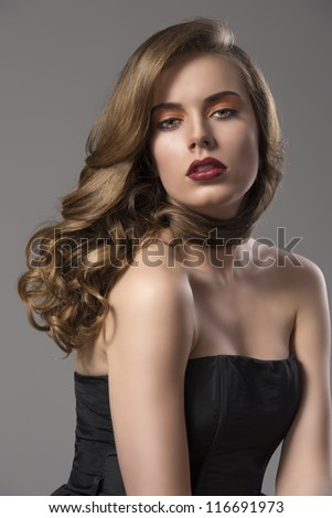 beautiful woman with long wavy hair and dark dress, looks in to the lens with sensual expression - stock photo