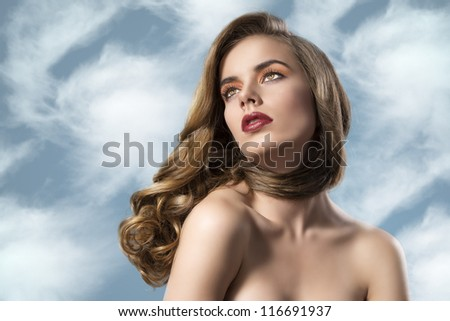 beautiful woman with long wavy hair and dark dress, she is turned at right and looks up - stock photo