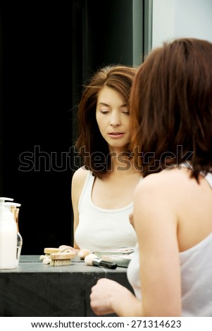 Beautiful woman with make up cosmetics in bathroom. - stock photo