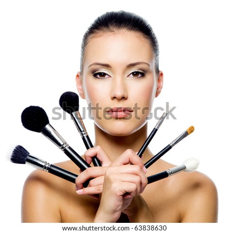 Beautiful woman with makeup brushes near her face - isolated on white - stock photo
