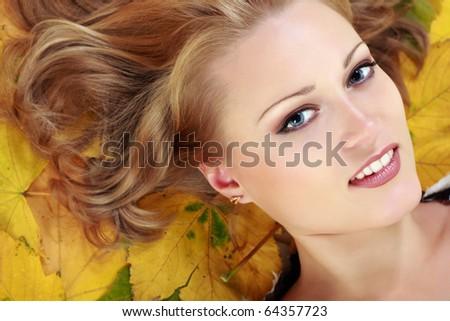 beautiful woman with maple leaves studio shot - stock photo